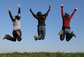 草原で青空に向かって思いっきりジャンプしている3人の女性